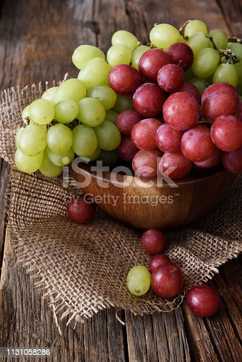 Fresh bunch of red and white grapes on a dark wooden background