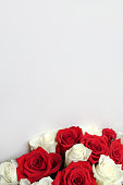 Bunch of red and white roses on blank surface with copy space for text. Backdrop for Saint Valentine's Day, International Women's Day, Mother's Day. Romantic greeting card, poster, invitation template