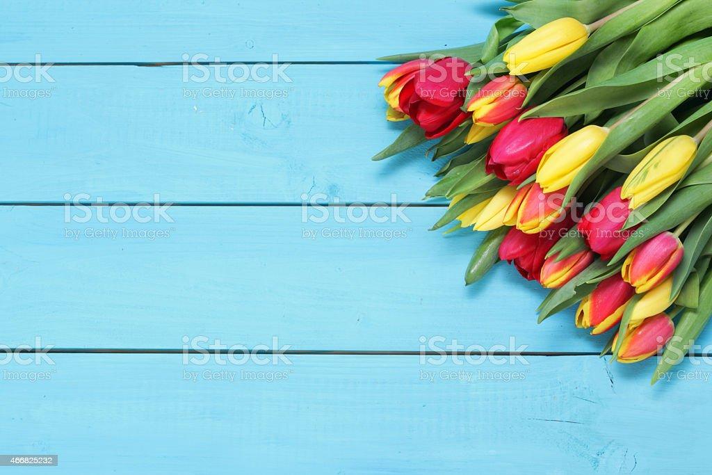 Mazzo di tulipani rossi e gialli con sfondo in legno for Mazzo per esterni in legno