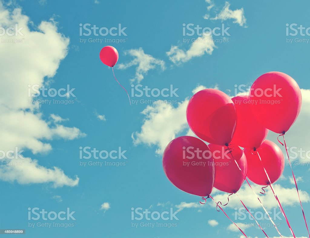 Bunch of red ballons on a blue sky Bunch of red ballons on a blue sky with one balloon escaping to be individual and free - concept for following one's dreams Aspirations Stock Photo