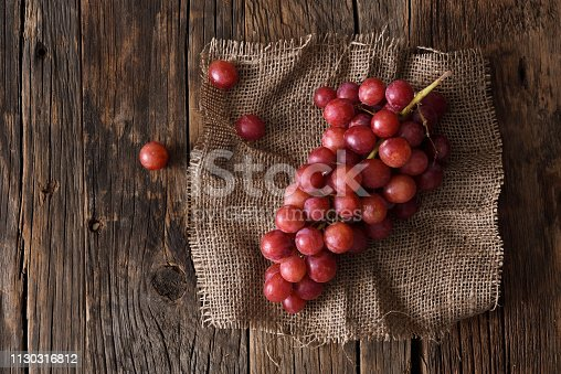 Fresh bunch of red grapes on a dark wooden background