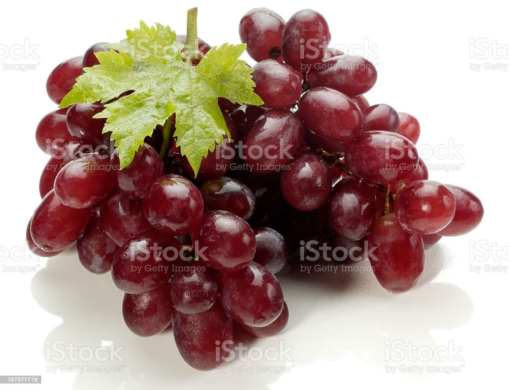 A bunch of red grapes with one green vine leaf royalty-free stock photo