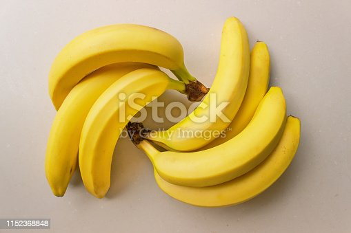 Bunch of ripe bananas on a light background. Concept- organic fruit, healthy food.