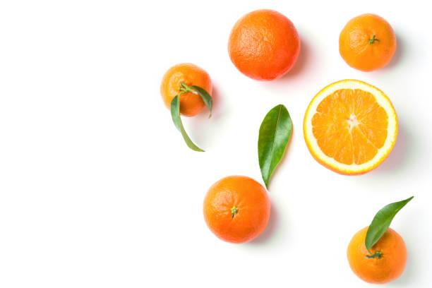 Bündel reifer saftiger organischer Orangenangerinen auf Ast mit grünen Blättern auf weißem Hintergrund. Flachblick flach gelegen. Vitamine gesunden Lebensstil vegan Superfoods Konzept. Kreatives Lebensmittelplakat – Foto