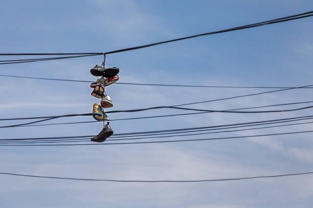 paar schuhe aus einem elektrischen draht hängen - kabelschuhe stock-fotos und bilder