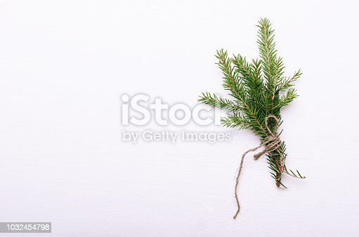 A bunch of small thorny evergreen fir branches wrapped in rope on a white background. Winter bouquet, New Year's mood. Copy space, top view