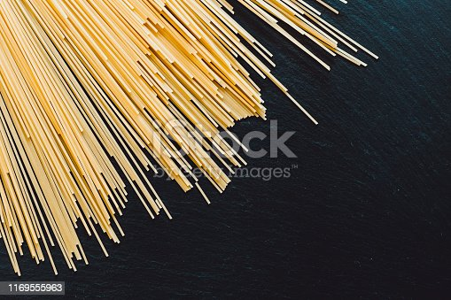 Bunch of long and thin spaghetti placed on the top of a black table as background with copy space - Gluten free pasta on stone textured surface