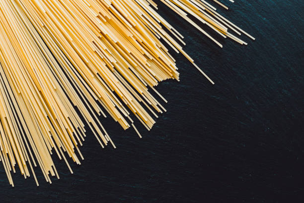 Bunch of spaghetti strand on the top of a black table as background stock photo