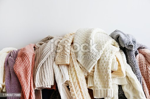 Categorizing winter laundry concept. A messy pile of knitwear lying on grey textile sofa. Bunch of unfolded sweaters prepared for sorting. Close up copy space, background.