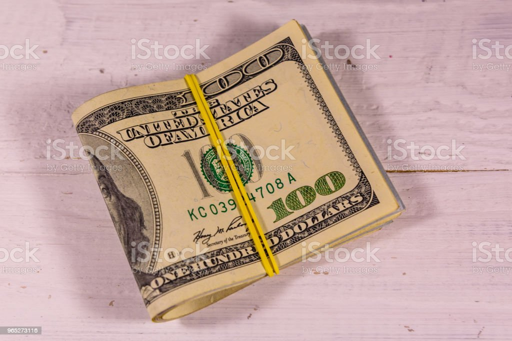 Bunch of the one hundred dollar bills with rubber on wooden table royalty-free stock photo