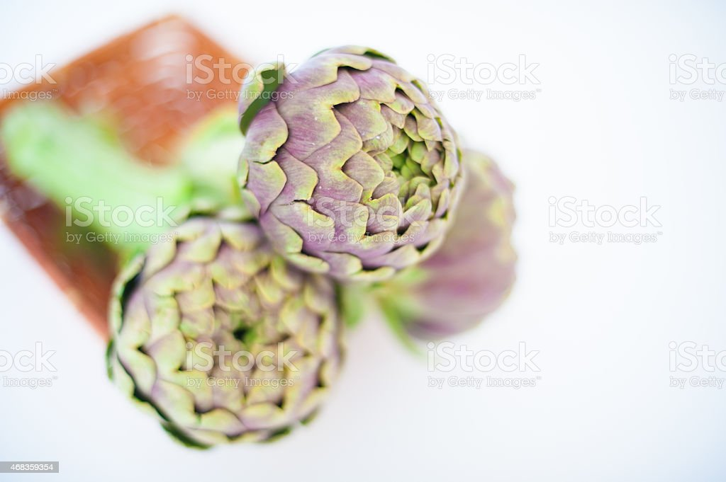 Bunch of three artichokes in basket on white background royalty-free stock photo