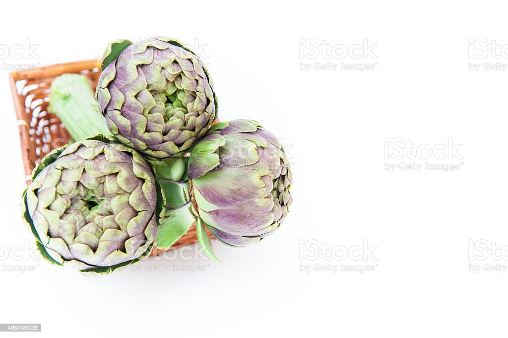 Bunch of three artichokes in basket white background royalty-free stock photo