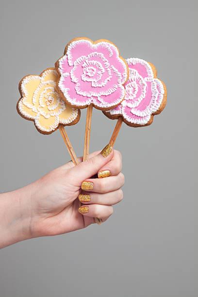 paar ungewöhnliche blumen: cake pops mit zuckergussverzierungen. - lutscher cookies stock-fotos und bilder
