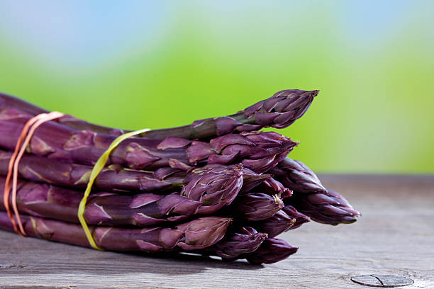 Bunch of violet asparagus on wood stock photo