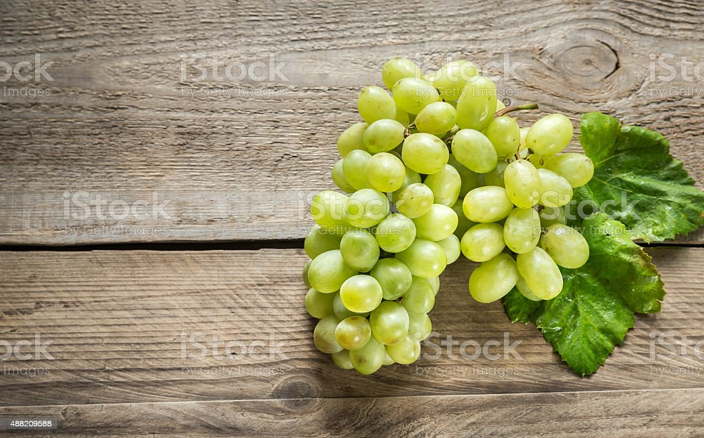 Bunch of white grape on the wooden background stock photo