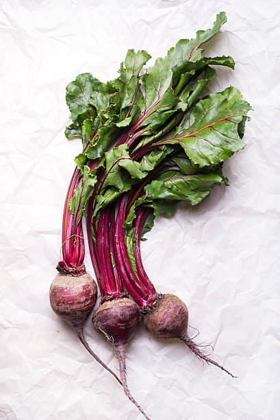 bunch of whole beetroots with green leaves on paper stock photo