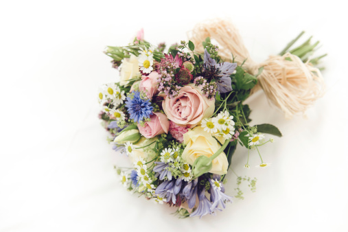 A beautiful bunch of wild flowers making up a wedding bouquet on a white background. Full of yellow and pink roses.