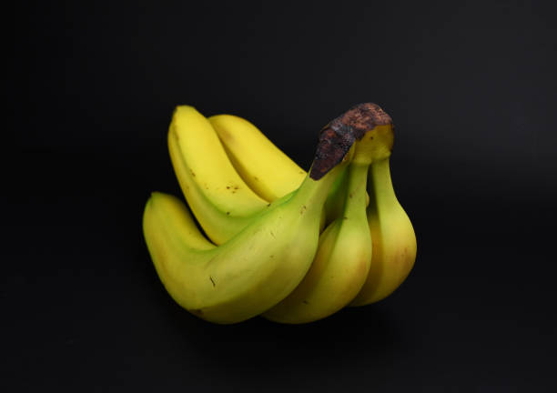 Bunch of yellow healthy bananas isolated on black background stock photo