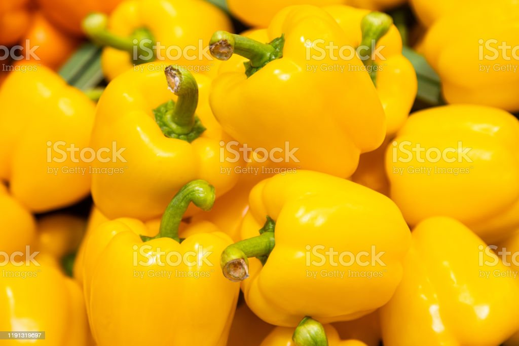 Bunch of yellow peppers in farmer's market or grocery store. Vegetable background. Spicy and sweet plant for sustainable diet. Bunch of yellow peppers in farmer's market or grocery store. Vegetable background. Spicy and sweet plant for sustainable diet Agriculture Stock Photo