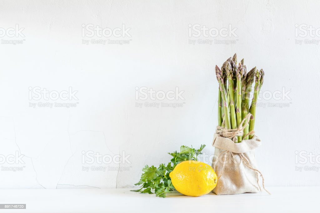Bunches of fresh asparagus in a little sack, lemon and fresh parsley on the white cracked wall background. Copy space stock photo