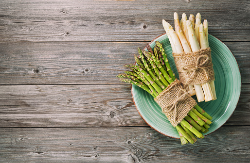 istock Bunches of fresh green and white asparagus on wooden background 935316576