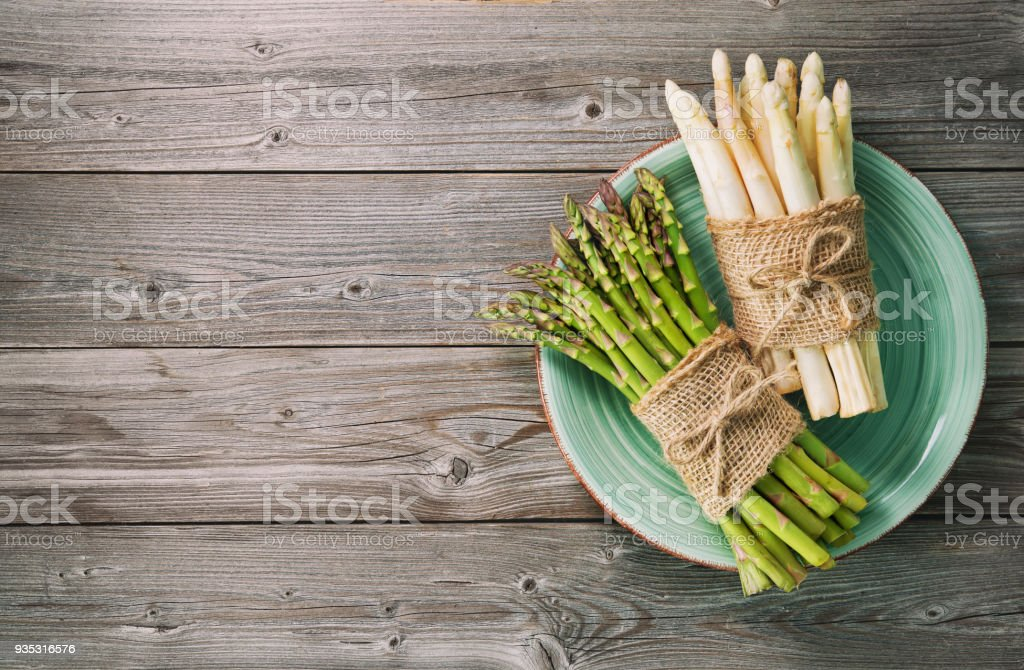 Bunches of fresh green and white asparagus on wooden background stock photo