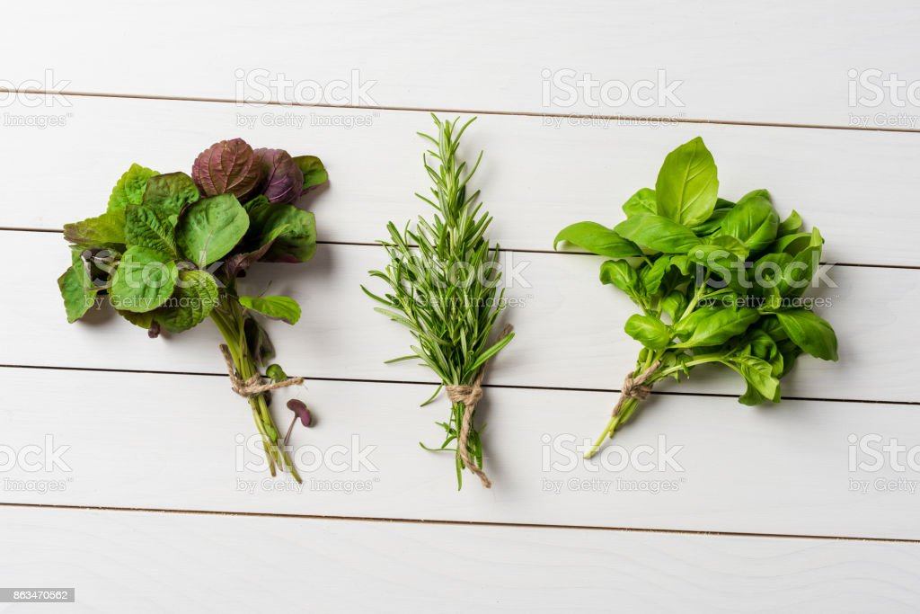 Bunches of fresh herbs on white wooden table. Close up