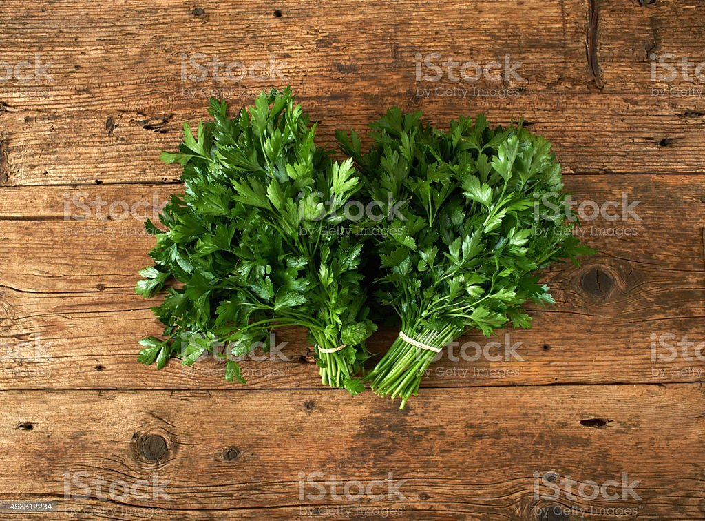 bunches of fresh parsley on wooden bench stock photo
