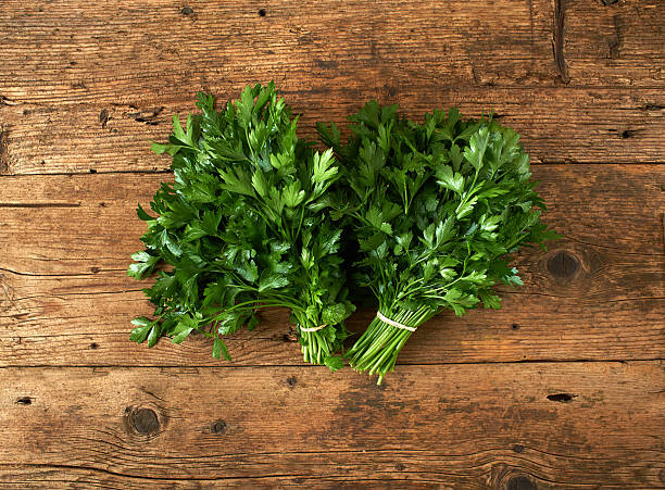 bunches of fresh parsley on wooden bench - parsley stock photos and pictures