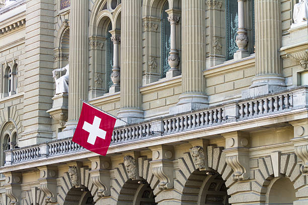 Bundeshaus Facade with Swiss Flag in Bern Bundeshaus Facade with Swiss Flag in Bern. swiss culture stock pictures, royalty-free photos & images