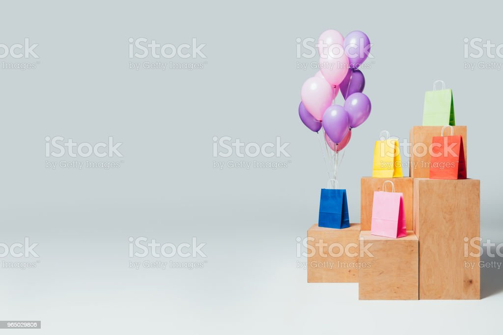 bundle of balloons near shopping bags on stands, summer sale concept royalty-free stock photo