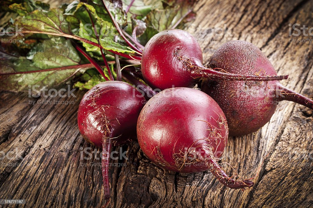 Bundle of beetroots with leaves on wooden table stock photo