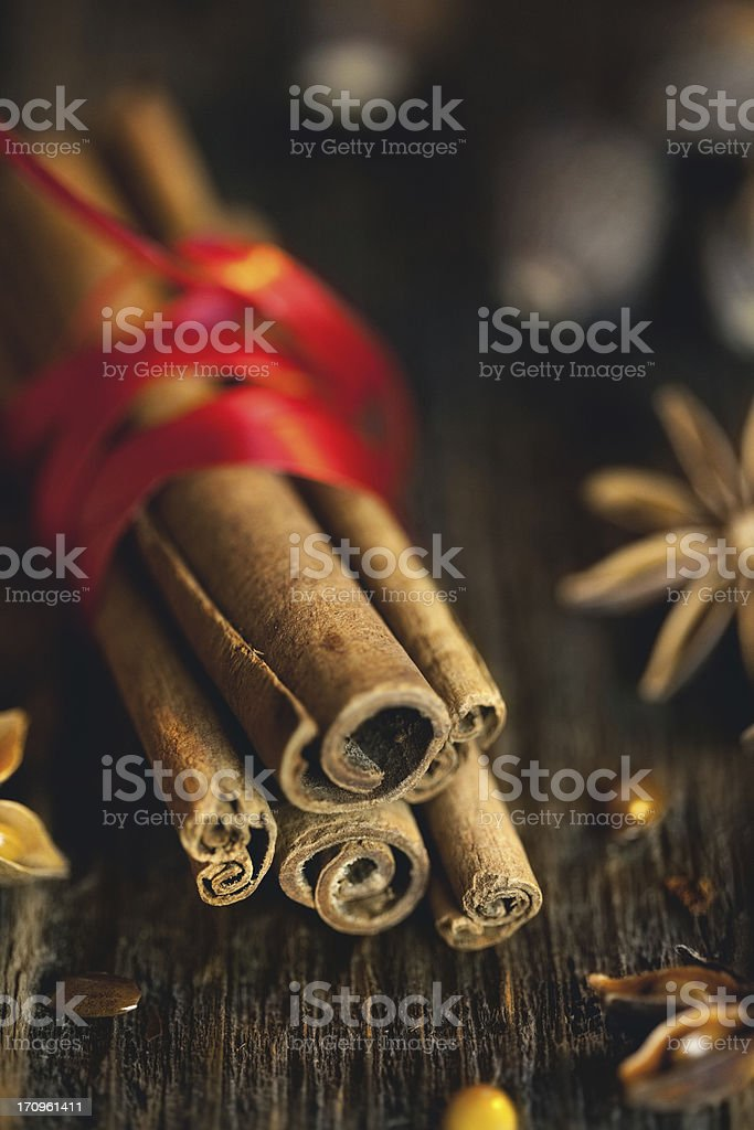 Bundle of cinnamon sticks and anis stars with seeds. royalty-free stock photo