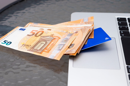 A bundle of euro banknotes and a bank card lie on a laptop. Close-up.
