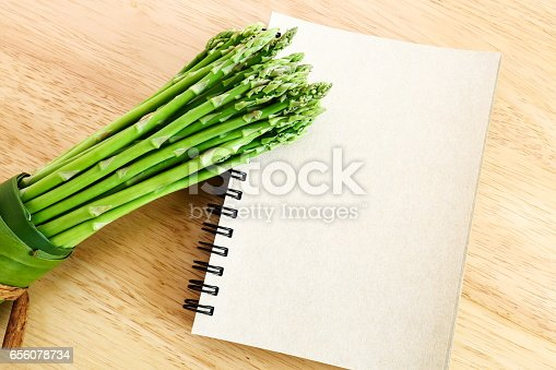 istock Bundle of fresh asparagus on wooden background. 656078734