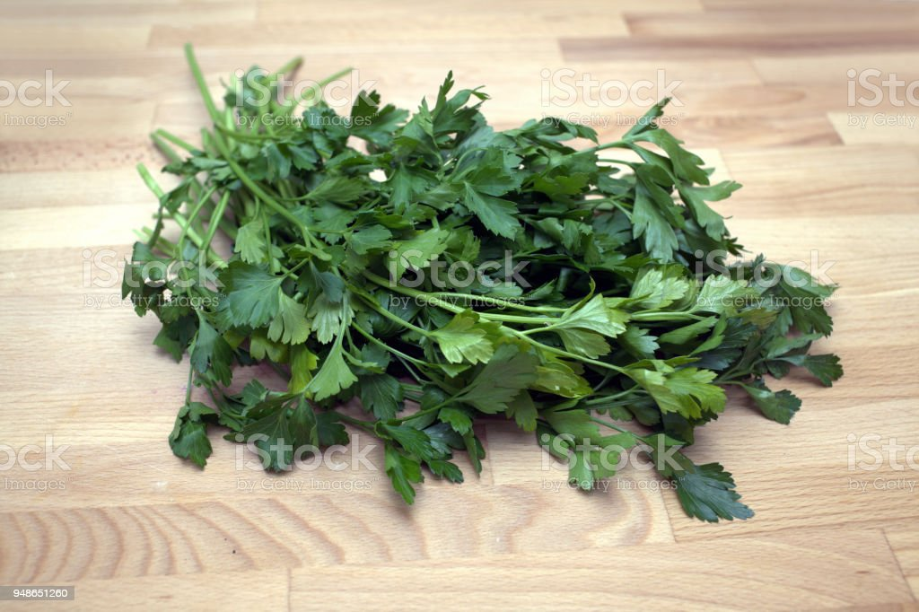 Bundle of fresh parsley lies on wooden surface of a table in the kitchen closeup stock photo