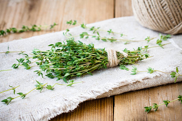 bundle of fresh thyme on sackcloth bundle of raw fresh organic thyme on sackcloth thyme photos stock pictures, royalty-free photos & images