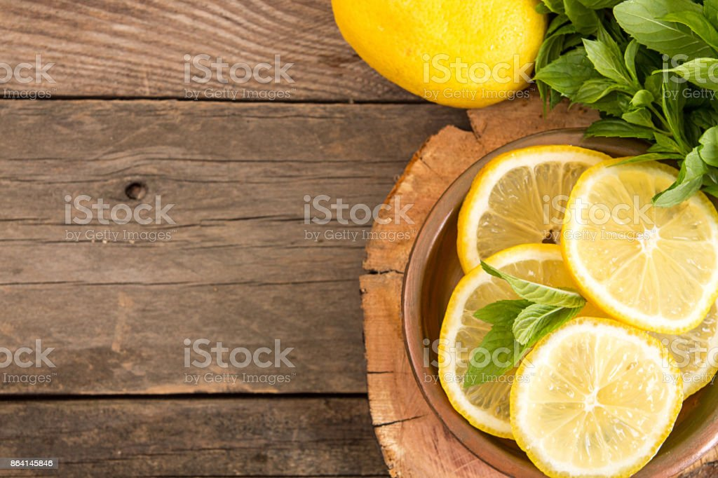 Bundle of mint and slices of lemon on old wooden background. Copy space. Top view. Rustic style royalty-free stock photo