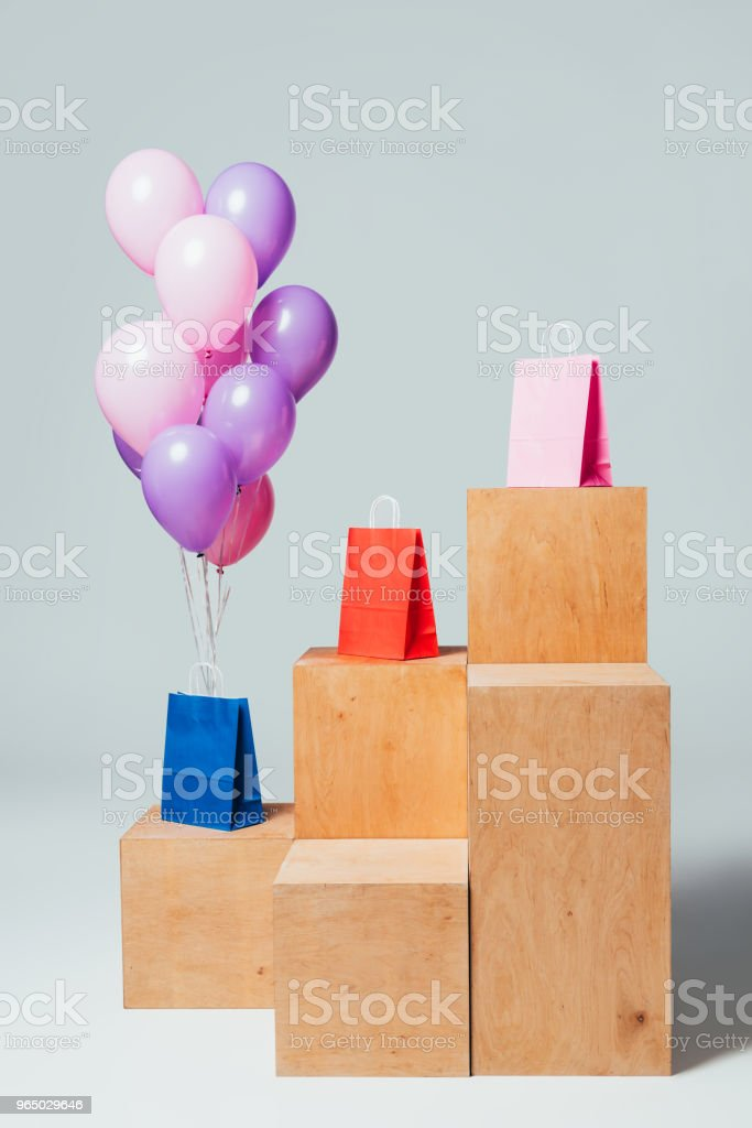 bundle of pink and violet balloons near paper bags on stands, summer sale concept royalty-free stock photo