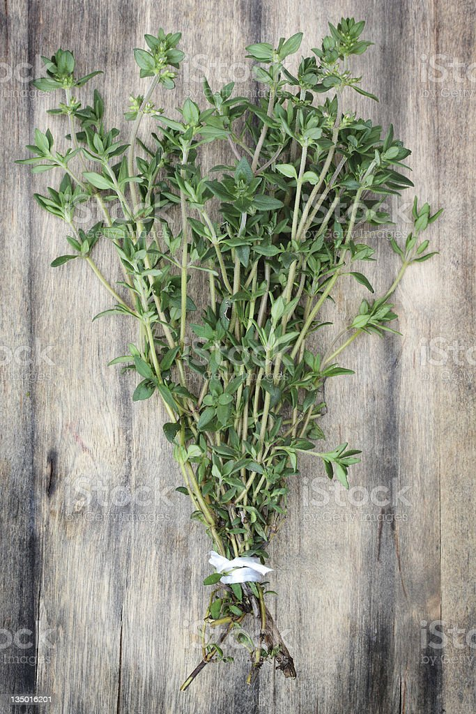 A bundle of thyme on a wooden surface stock photo