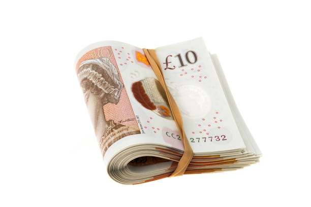 Bundle of UK ten pounds banknotes A wad of UK ten pounds banknotes - studio shot with a white background ten pound note stock pictures, royalty-free photos & images