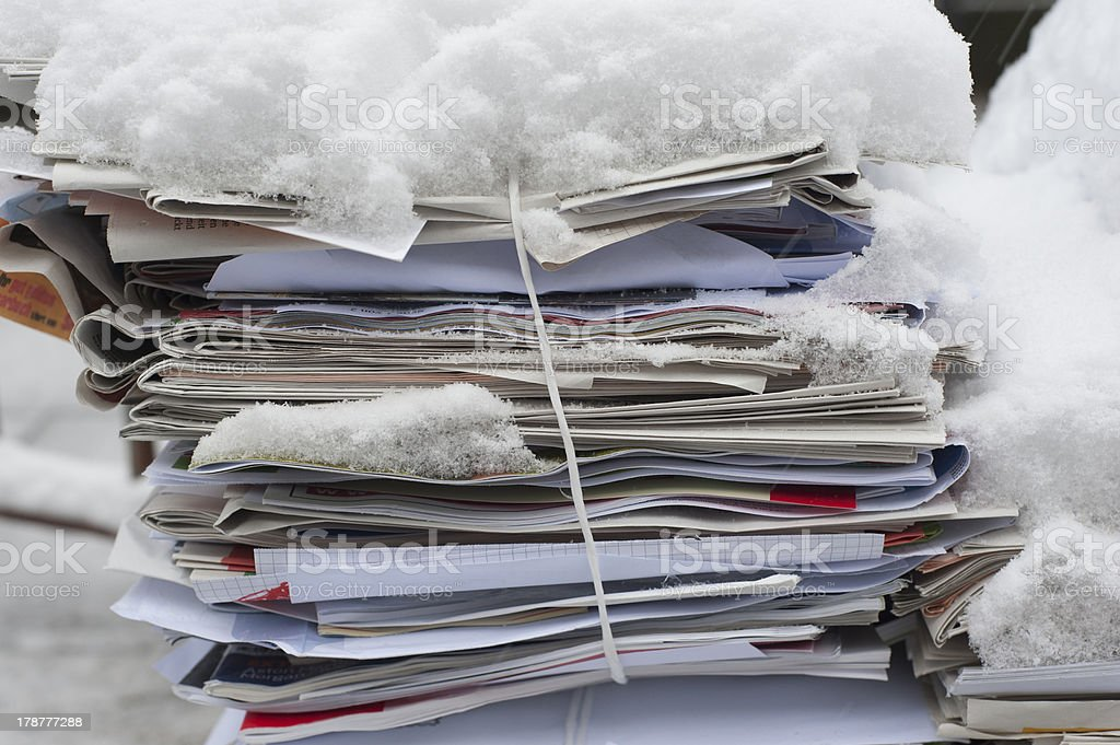 Bundled newspapers in the snow royalty-free stock photo