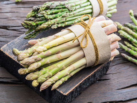 Bundles of green and white asparagus on wooden board.
