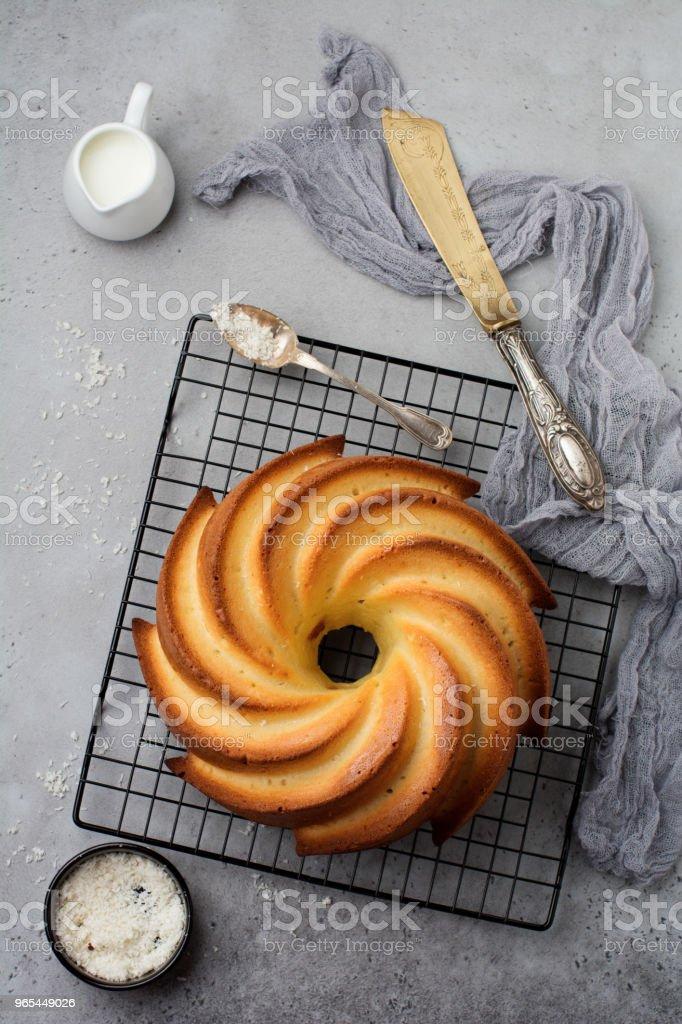 Bundt cake with sugar glaze and coconut on dark grey old concrete background. Selective focus. Top view with copy space. zbiór zdjęć royalty-free