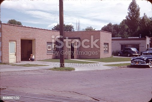 Los Angeles, California, USA, 1953. Typical California bungalow in Los Angeles. There is a young woman sitting in front of the open garage door. The bungalow is on a road corner. On the street is a parked car.