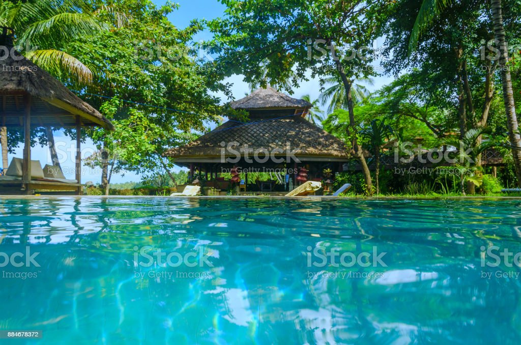 bungalow on pool in Bali - split view on pool water - summer paradise stock photo
