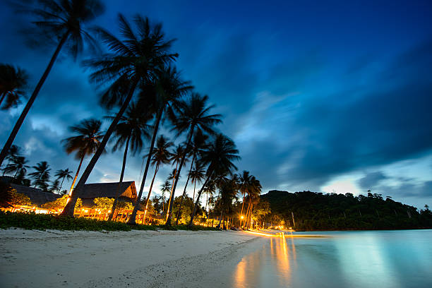 Bungalows, palms and beach at sunset in thailand paradise stock photo