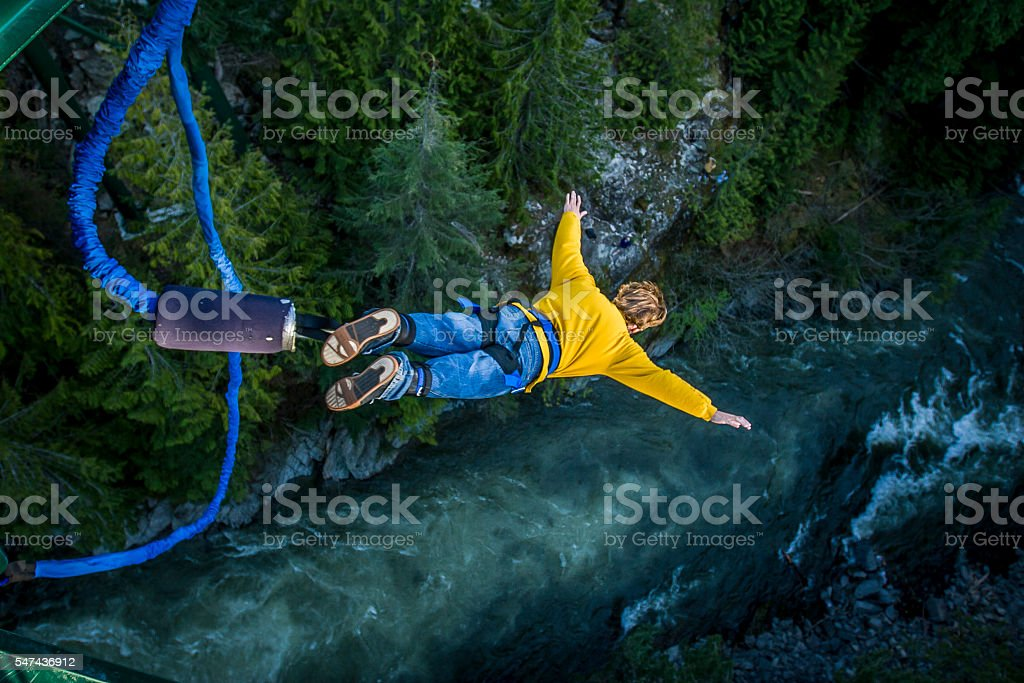 Bungee jumping. Young man bungee jumping over river. Achievement Stock Photo