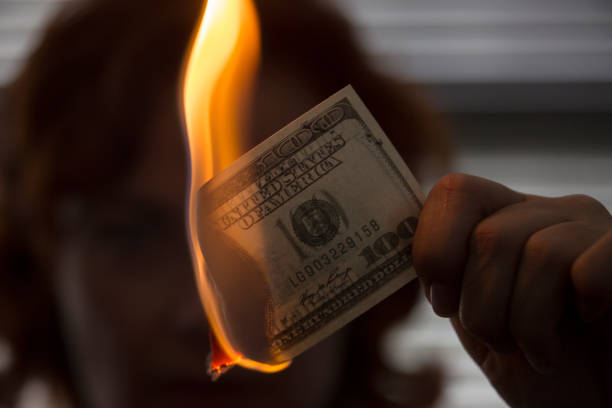 Buning money Person hold a burning $100 dollar note money to burn stock pictures, royalty-free photos & images