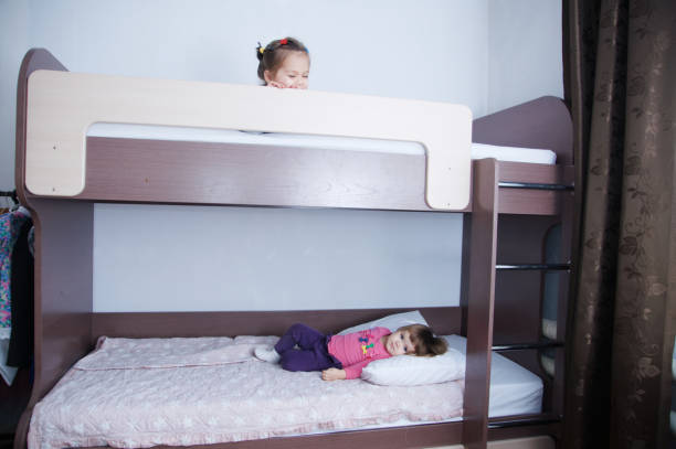 etagenbett in kind room.two kleines mädchen spielen auf bett. schokolade schatten im innenraum mit weißen wänden. dunkelbraune möbel für kinder wohnraum - etagenbett weiss stock-fotos und bilder